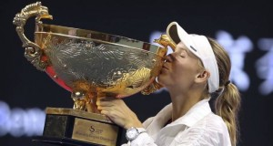 Caroline Wozniacki besa el trofeo que la acredita como campeona del Abierto de China tras vencer a la letona Anastasija Sevastova en la final de mujeres en Beijing. (AP Foto Mark Schiefelbein)